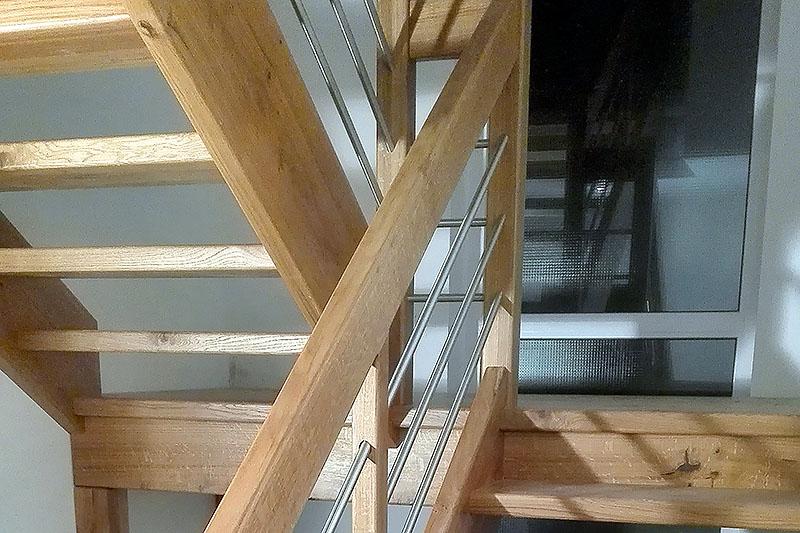 Holztreppe mit Metalleinlage im Geländer